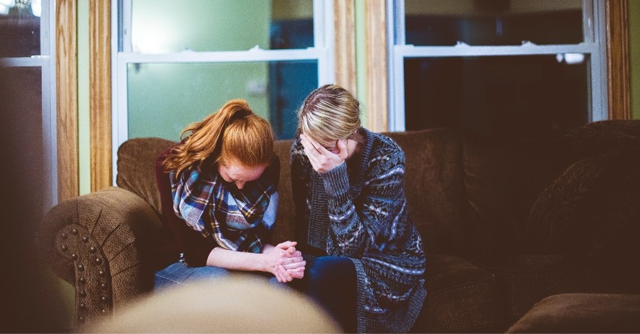 Praying women on a couch, Remember the sanctity of home as we return to physical churches