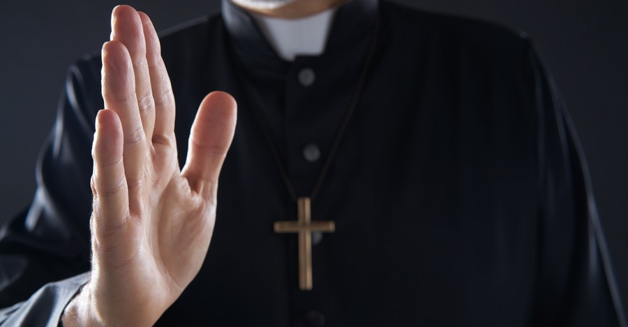 Catholic priest raising hand in blessing