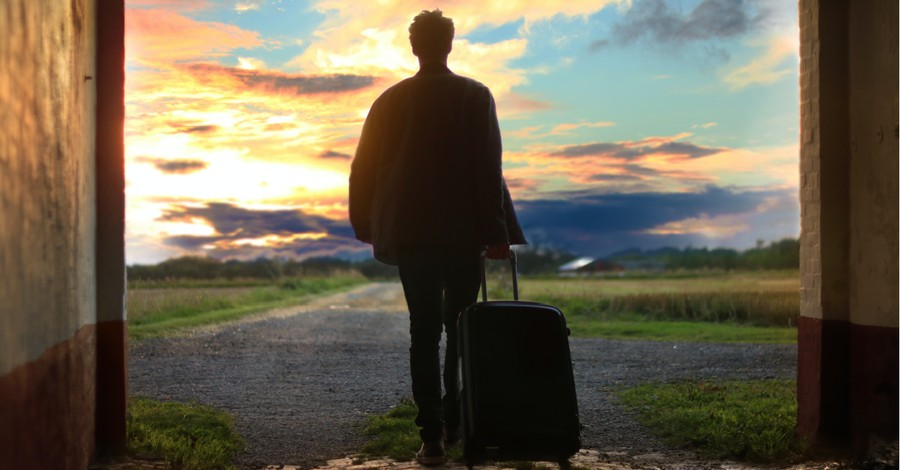a man walking away with a suitcase, how being a guest liberates us