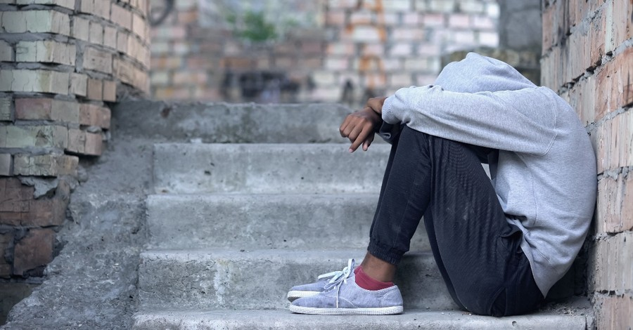 young teen boy sitting alone on steps looking in need, prayer to soften hearts for vulnerable