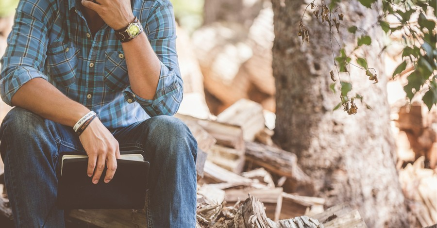 A pondering man with a Bible in the woods, Leading in unprecedented times