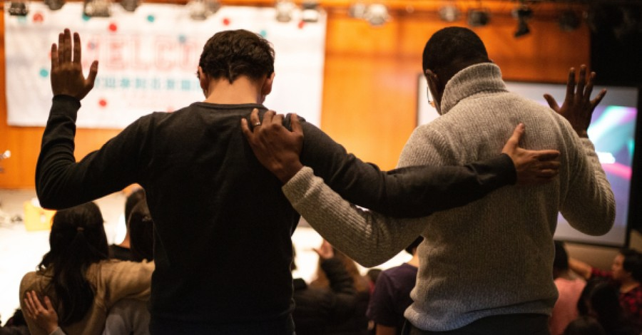 A white and a black man praying together, How Can Christians Help to Heal the Racial Divide?