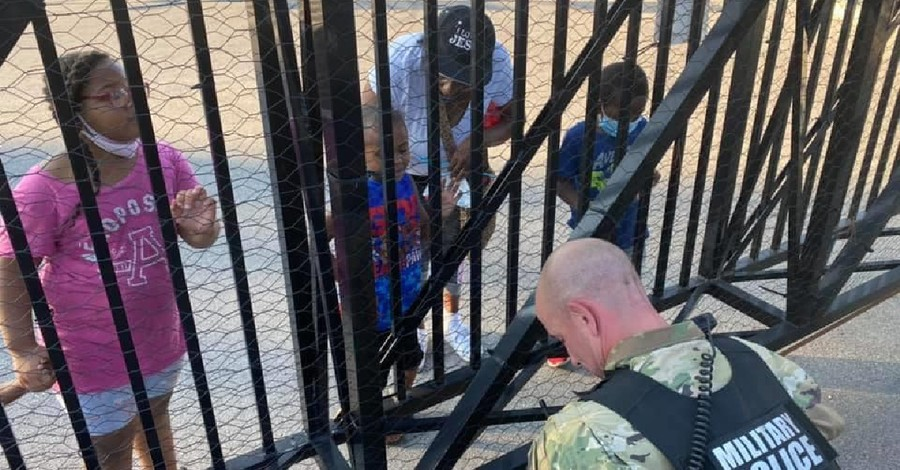 A National Guard Member praying with a child, 5-year-old boy prays with a National Guard member amid protests