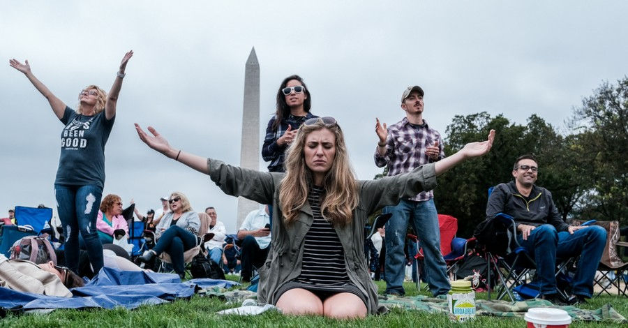 People praying in front of the Washington Monument, Thousands gather in D.C. to pray over the nation