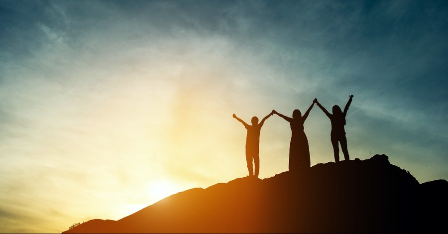 Women on a mountain with their arms up