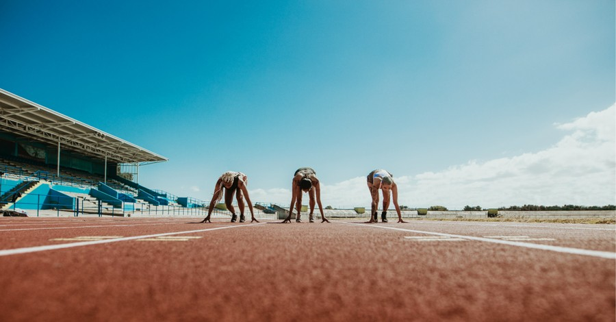 women running on a track, bill proposes schools allowing biological males athletes who identify as female to compete in sports be defunded