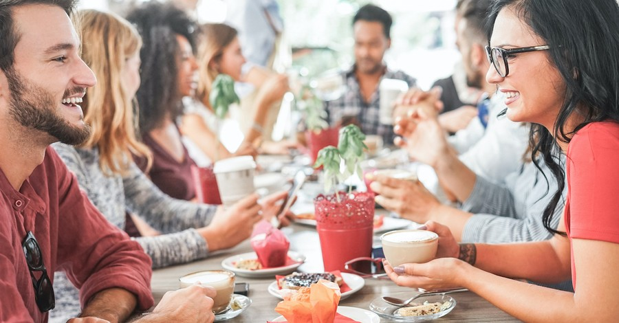 group of friends having brunch together happily at table, eat drink and be merry