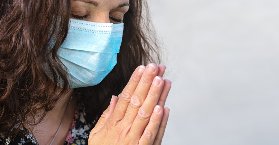 woman with coronavirus face mask praying for school year