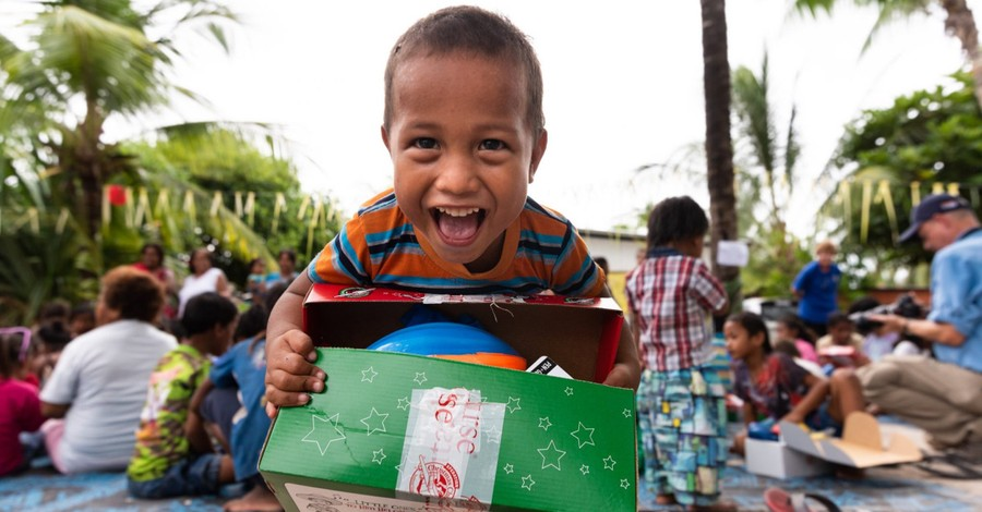 A kid with an OCC shoe box, Operation Christmas Child is making a huge difference