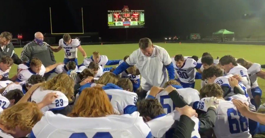 A football coach Praying with his team, Football coach is asked to stop praying with team