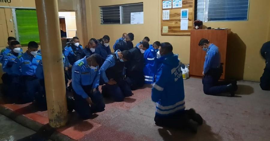 Honduran Police praying, Police and church members prayer for national healing following Hurricane Iota