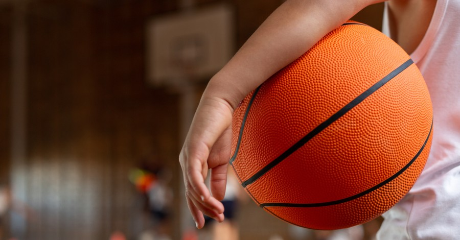 A kid holding a basketball, what churches can do for kids with disabilities