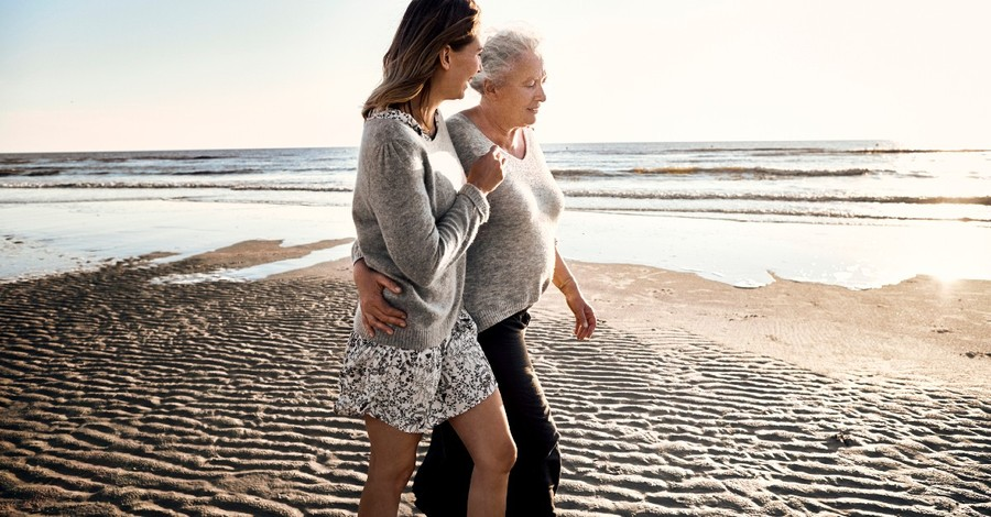 A woman walks her elderly mother along the beach at morning