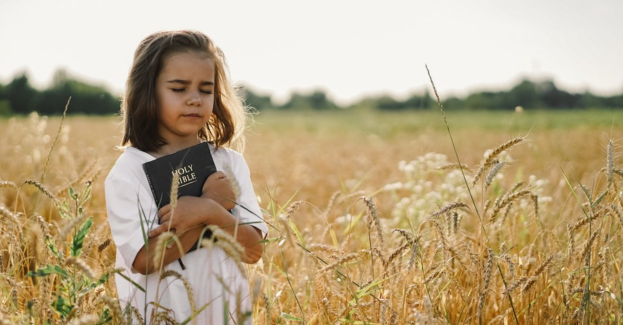 little girl holding Bible outside in a field with her eyes closed, Bible verses for kids