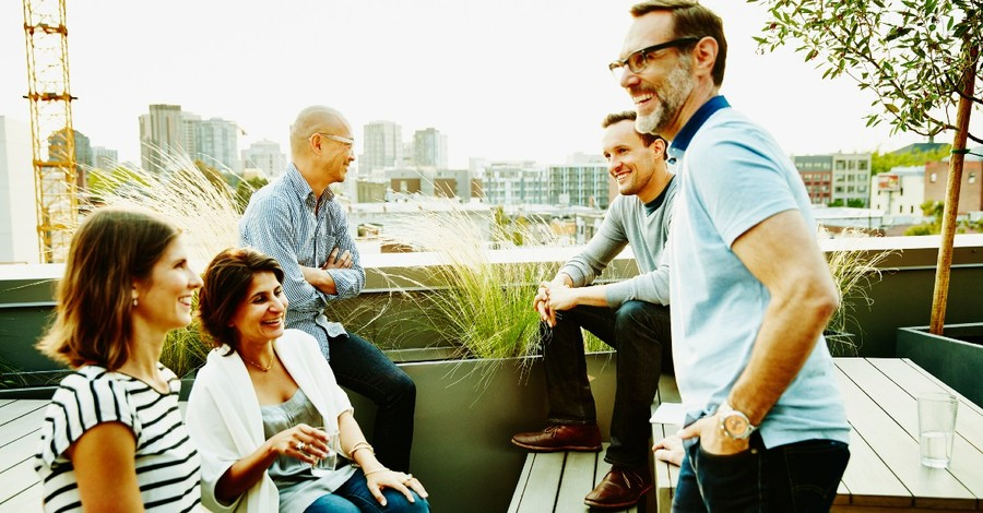 A group of middle aged friends gather on a balcony overlooking a river