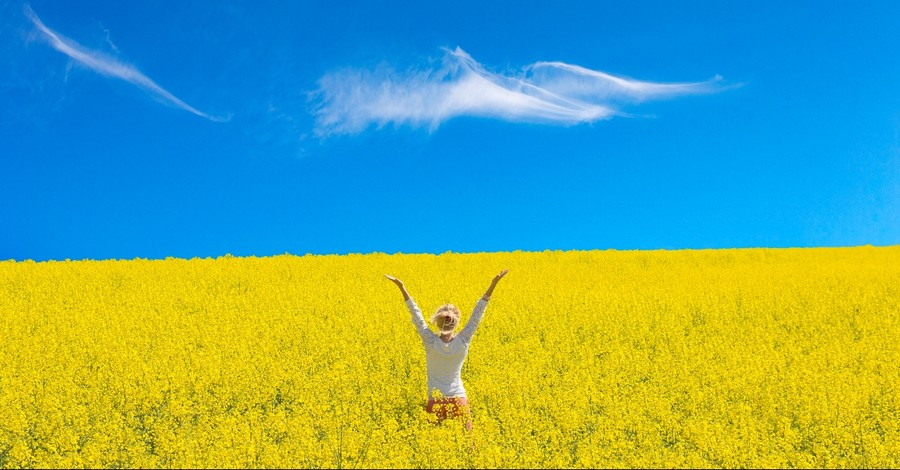 Woman with her hands up in a yellow field