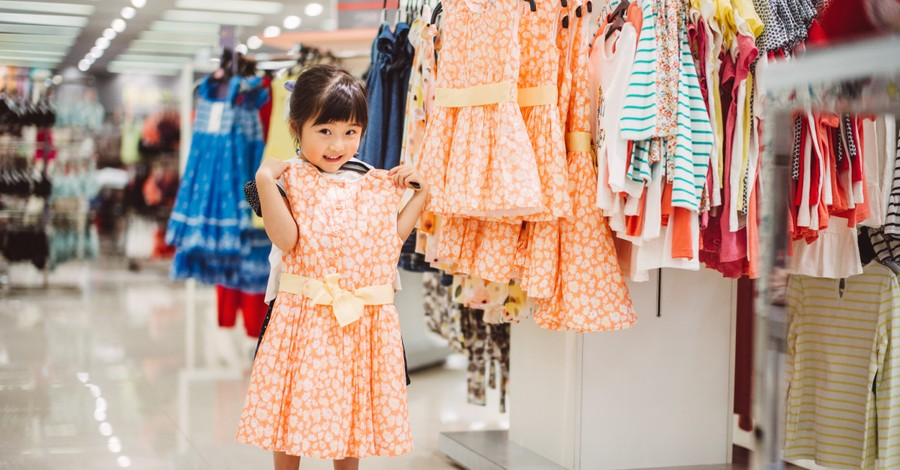 little girl holding dress, CA bill would fine retailers $1000 for having separate girls and boys sections