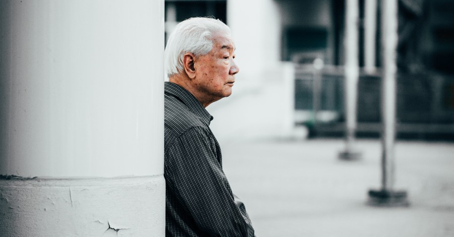an Asian man sitting outside, Asian American hate crimes have jumped by 150 percent