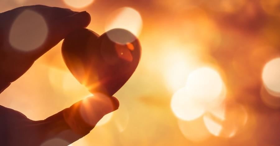 hand holding heart up to light, god is love john 4:8