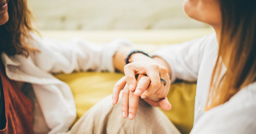 two women holding hands, church is under fire after they expelled a woman who divorced her husband and came out as lesbian