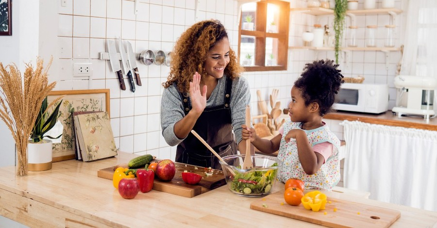 A mom high-fives her daughter as they prepare a healthy dinner
