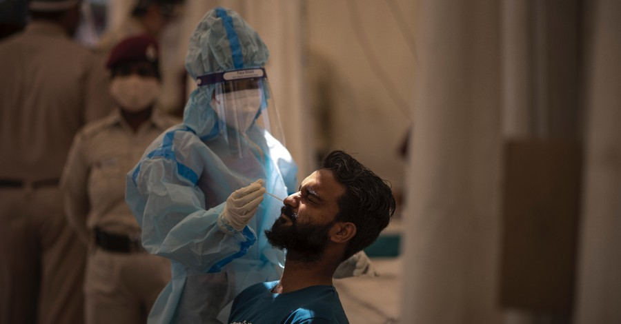 Doctor in India administering a COVID test, India records more than 320,000 new covid cases