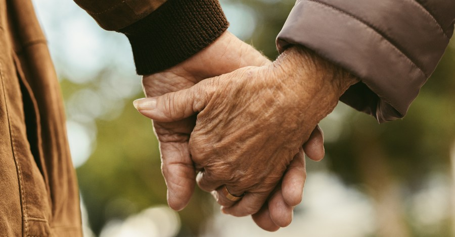Elderly couple holding hands, couple celebrates 70 years of marriage and thanks God