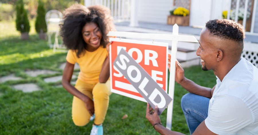 A couple putting up a sold sign, survey reveals that 1/3 of young people in America see property ownership as a bad thing