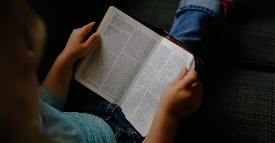 a little girl reading a Bible, Illinois school reverses course after banning girl from reading her Bible