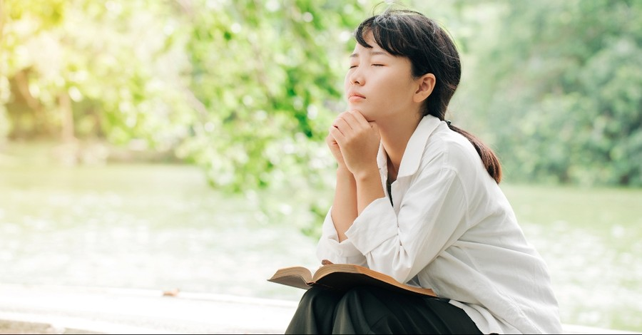 Woman praying with a Bible on her lap