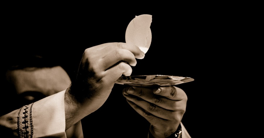 Priest holding the eucharist, Bishops clarify that they are not banning pro-choice politicians from partaking in Communion