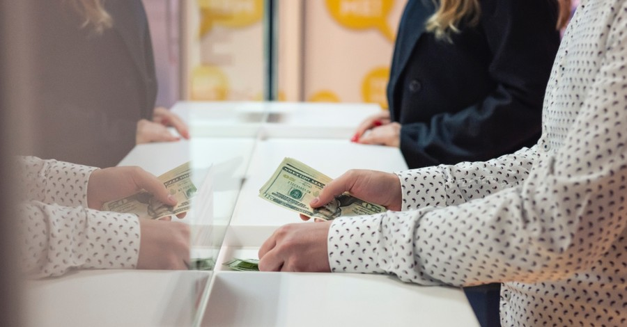 person exchanging money, Evangelist forms pro-life bank