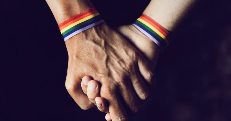 Two people holding hands and wearing rainbow bracelets, Federal court uphold Colorado Anti-discrimination law