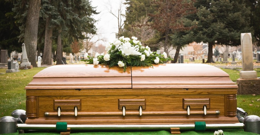 A coffin with flowers on it, pastor's wife commits suicide