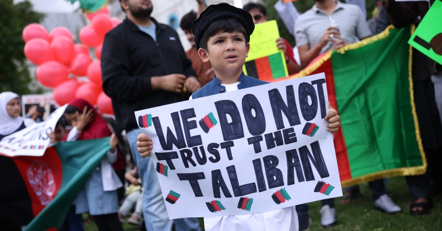 a young boy holding and Anti-Taliban sign, The internal logic of the Taliban