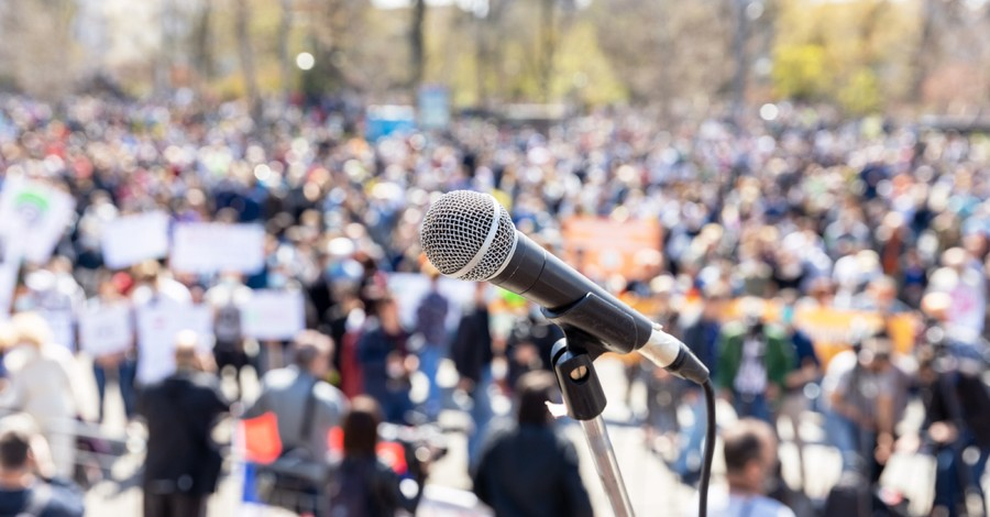 a microphone on stage, hundreds gather to march in honor of persecuted Christians