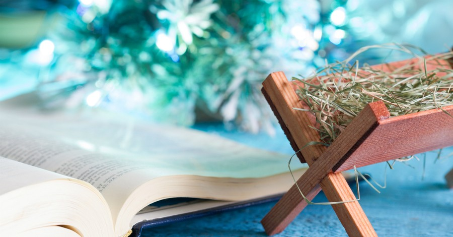 Tiny manger next to open Bible