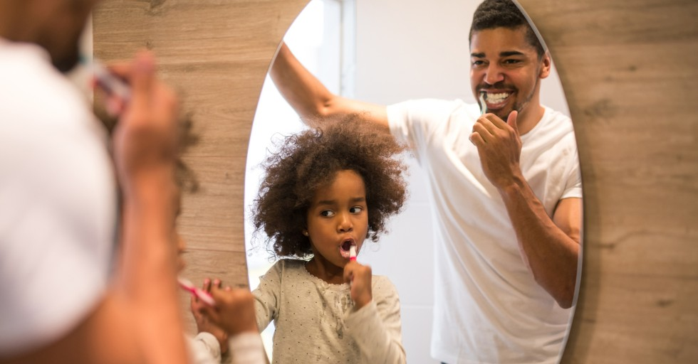 dad and daughter brushing teeth in mirror