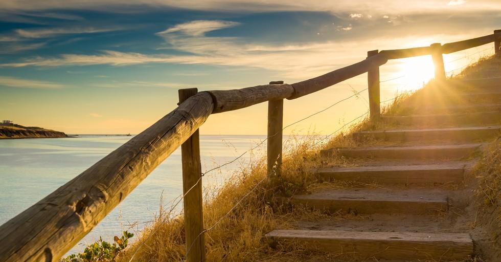 Escalera pacífica colina arriba en la playa al atardecer